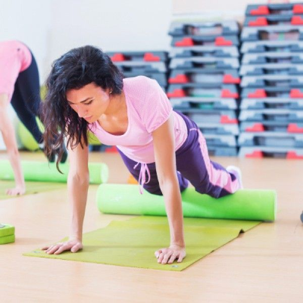 Fit woman stretching on floor using foam roller doing plank exercise, push ups.