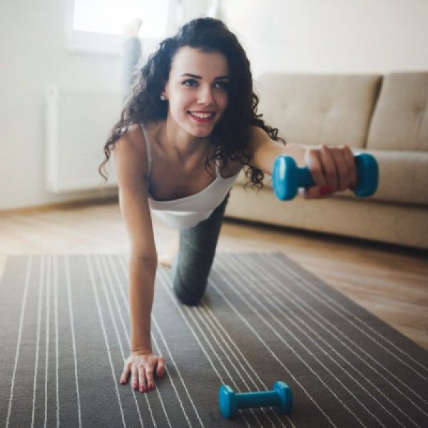 Happy determined woman working out with dumbbells at home
