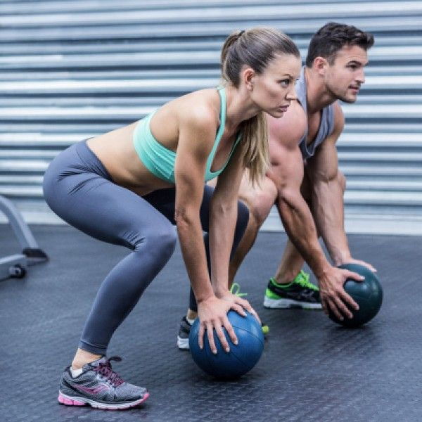 Squatting muscular couple doing ball exercise