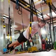 Crossfit fitness TRX push ups man workout at gym