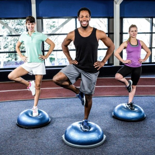 Fit people doing exercise with bosu ball in crossfit