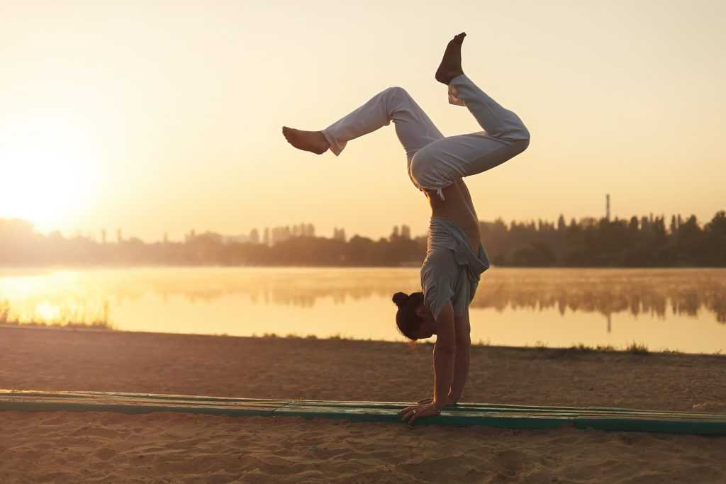 Athletic yoga man workout training on the beach sunrise